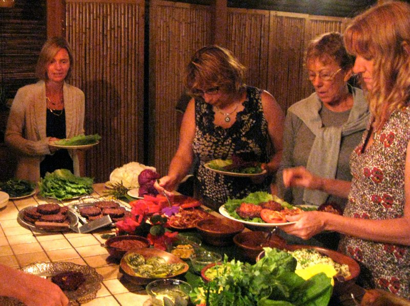 Women gather around a dinner buffet at Farm of Life